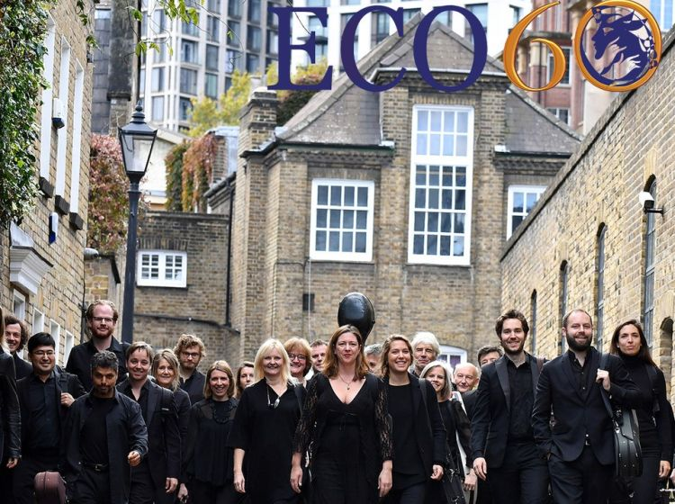 The English Chamber Orchestra walk along a street in black clothes towards the camera