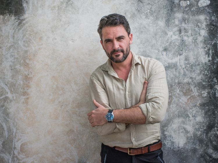 Explorer and author Levison Wood stands in a casual shirt and jeans against a grey background